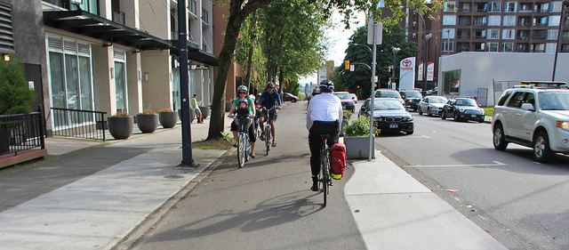 Family riding bicycles in city.